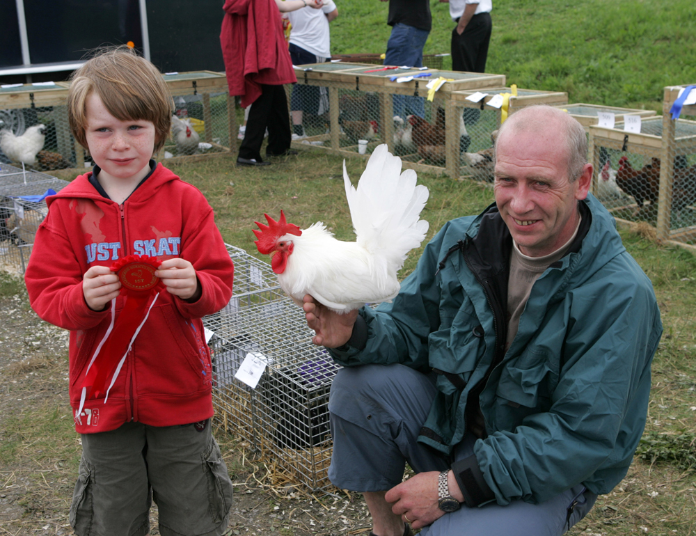 John Kenneth Dowling, Crossmolina holding his red rosette for his Bantan Cock, at the 88th Claremorris Agricultural Show, pictured with his dad John Dowling. Photo: © Michael Donnelly