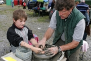 Paddy Rolleston, Beltra, Co Sligo assists novice potter Joe Cooley Claremorris at the Potters wheel, at the 88th Claremorris Agricultural Show. Photo: © Michael Donnelly